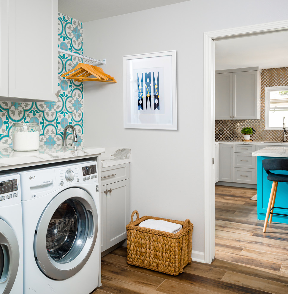 Small transitional single-wall porcelain tile and brown floor dedicated laundry room photo in Houston with an undermount sink, shaker cabinets, gray cabinets, solid surface countertops, gray walls, a side-by-side washer/dryer and white countertops