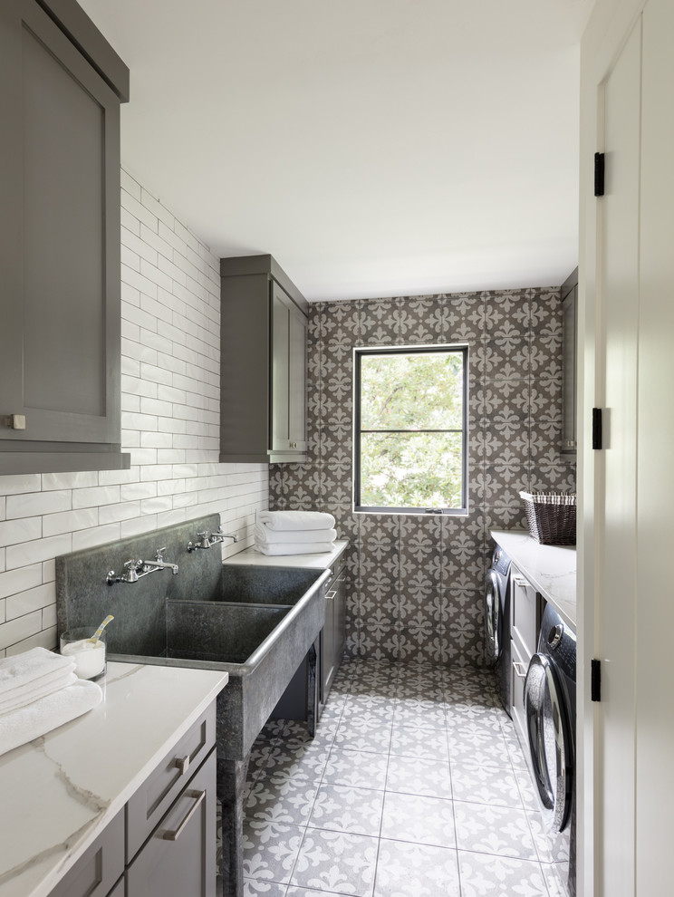 Inspiration for a farmhouse galley multicolored floor dedicated laundry room remodel in Denver with an utility sink, shaker cabinets, gray cabinets, a side-by-side washer/dryer, white countertops and gray walls