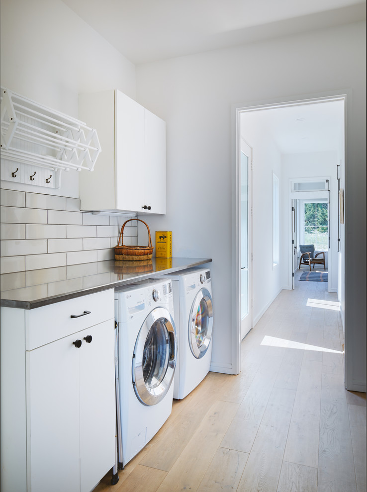 Example of a danish single-wall light wood floor and beige floor dedicated laundry room design in Austin with flat-panel cabinets, white cabinets, stainless steel countertops, white walls, a side-by-side washer/dryer and gray countertops