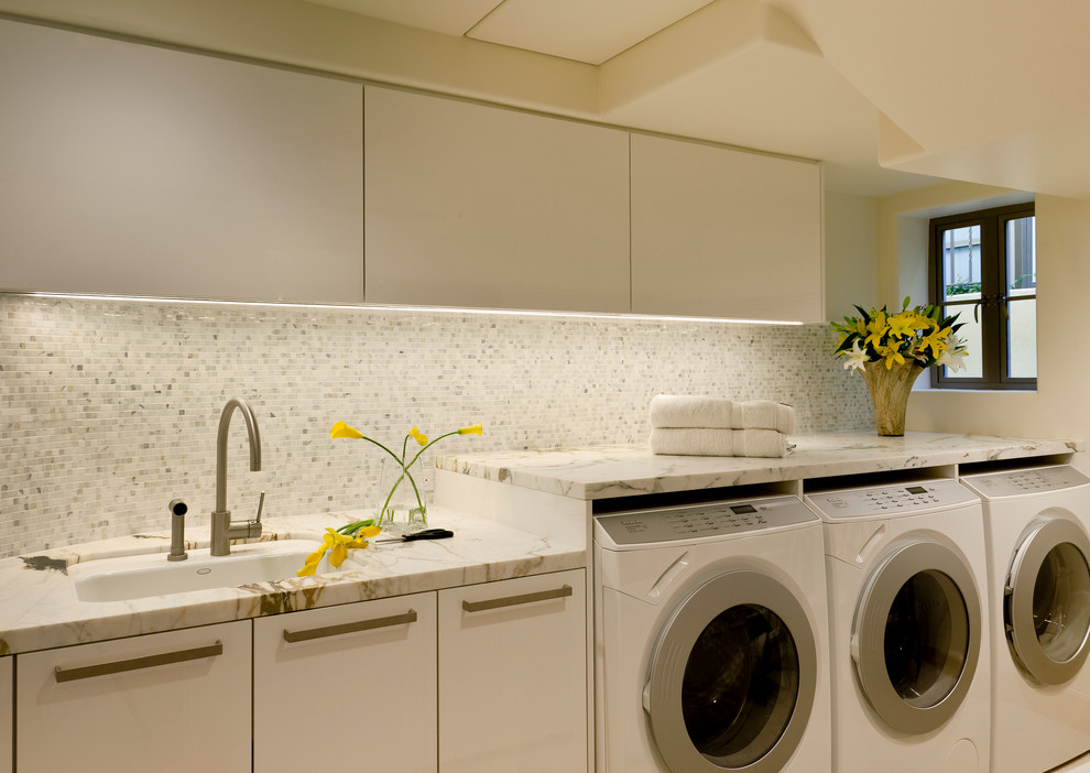 Example of a trendy laundry room design in Los Angeles with an undermount sink and white countertops