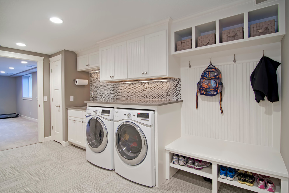 Utility room - large traditional single-wall ceramic tile and gray floor utility room idea in Minneapolis with white cabinets, a side-by-side washer/dryer, an undermount sink, shaker cabinets, solid surface countertops, beige countertops and gray walls