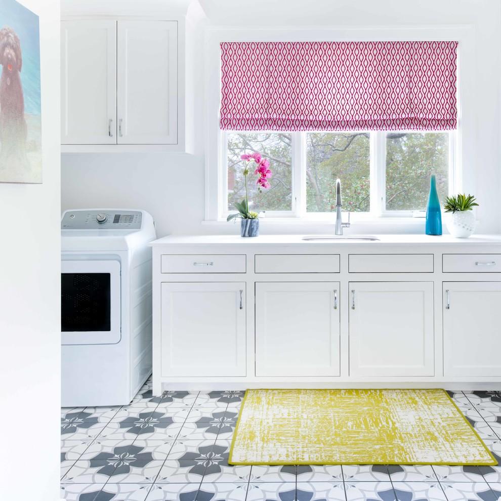 Modelo de cuarto de lavado marinero con fregadero bajoencimera, armarios estilo shaker, puertas de armario blancas, paredes blancas, suelo multicolor y encimeras blancas