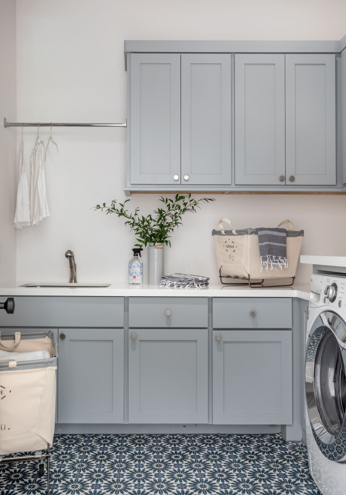 Huge transitional u-shaped ceramic tile and multicolored floor dedicated laundry room photo in Houston with a drop-in sink, gray cabinets, white walls, a side-by-side washer/dryer and white countertops