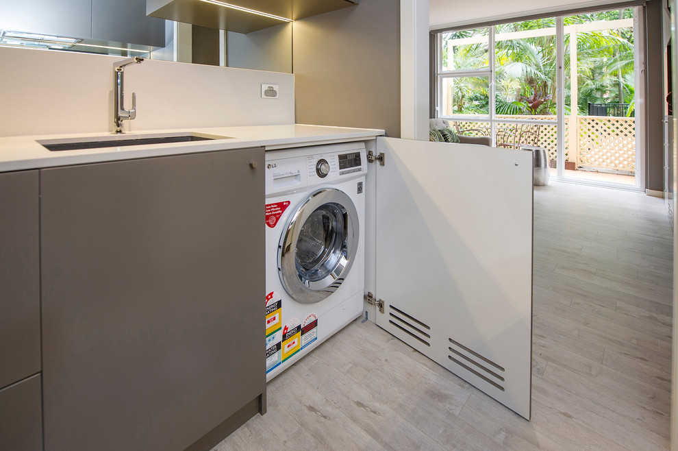 Inspiration for a small contemporary galley light wood floor utility room remodel in Sydney with a single-bowl sink, flat-panel cabinets, solid surface countertops and a concealed washer/dryer