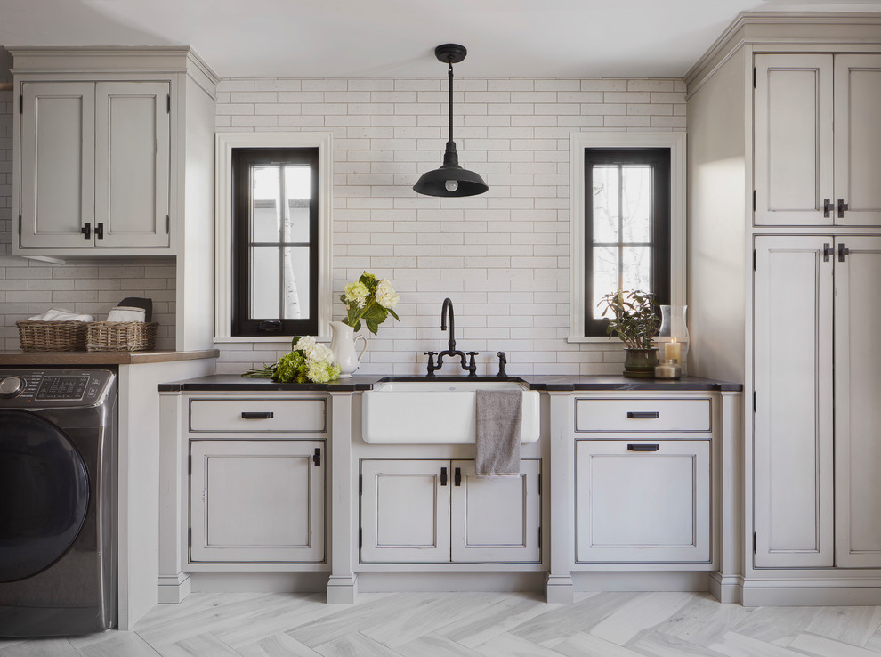Dedicated laundry room - large cottage single-wall porcelain tile and gray floor dedicated laundry room idea in Denver with a farmhouse sink, recessed-panel cabinets, gray cabinets, soapstone countertops, white walls, a side-by-side washer/dryer and black countertops