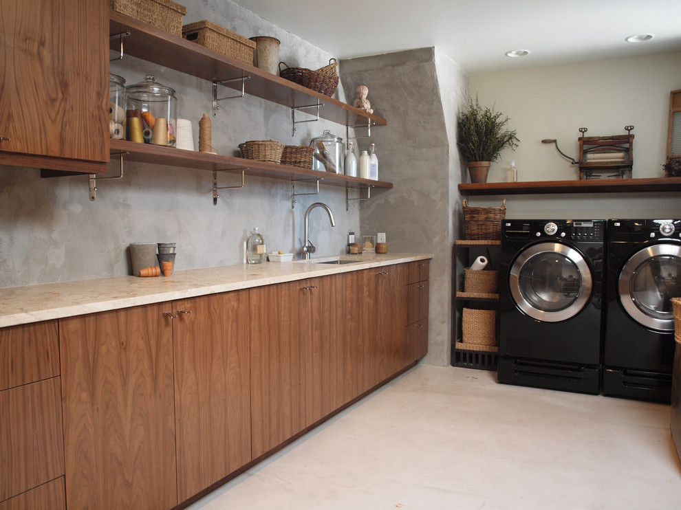 Example of a mid-sized trendy l-shaped beige floor utility room design in Chicago with flat-panel cabinets, a side-by-side washer/dryer, an undermount sink, medium tone wood cabinets, limestone countertops, gray walls and beige countertops