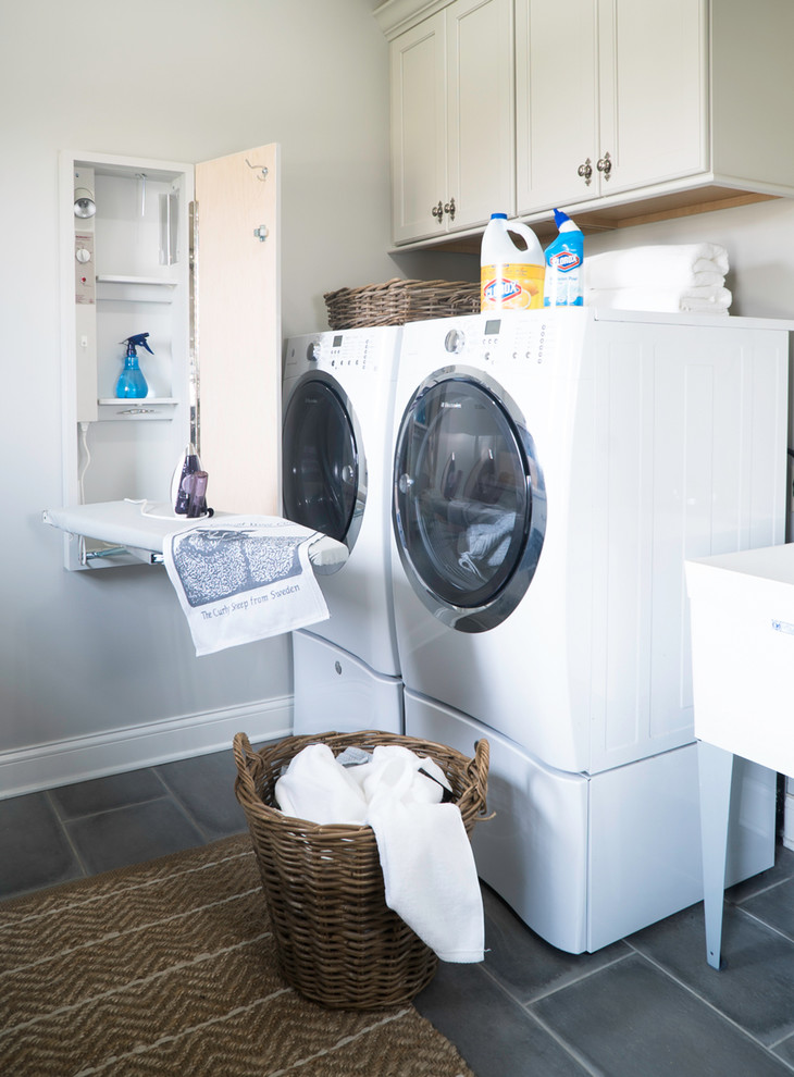 Mid-sized farmhouse porcelain tile and gray floor laundry room photo in St Louis with white cabinets, quartz countertops, beige walls, a side-by-side washer/dryer, recessed-panel cabinets and an utility sink