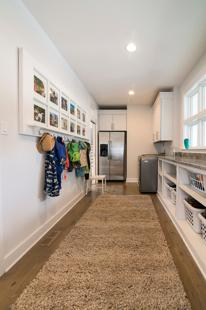 Example of a large cottage medium tone wood floor utility room design in Baltimore with open cabinets, white cabinets, laminate countertops, white walls and a side-by-side washer/dryer