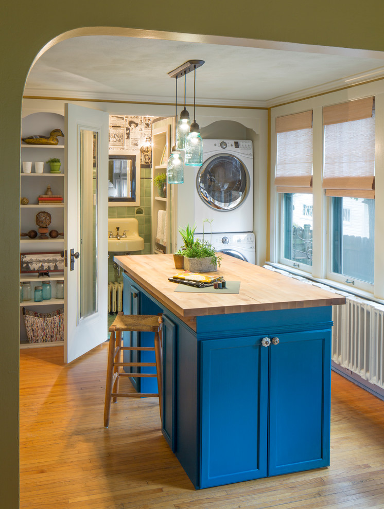 Laundry room - farmhouse laundry room idea in Chicago with open cabinets, blue cabinets, wood countertops and a stacked washer/dryer