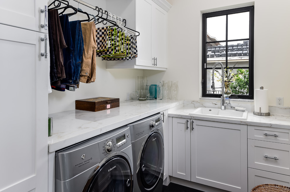 Example of a small transitional l-shaped dark wood floor and brown floor dedicated laundry room design in Miami with a drop-in sink, shaker cabinets, white cabinets, marble countertops, white walls, a side-by-side washer/dryer and white countertops