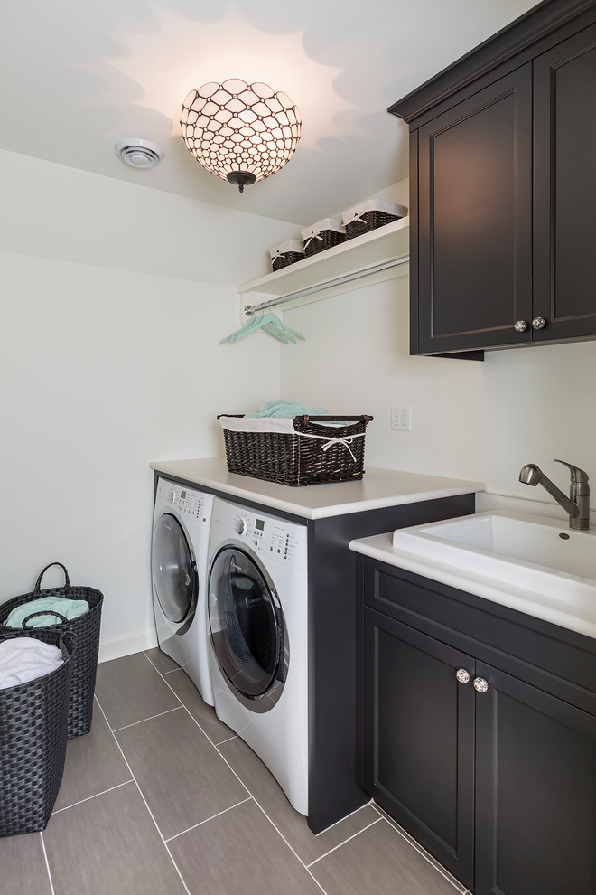 Example of a mid-sized transitional single-wall porcelain tile dedicated laundry room design in Minneapolis with a drop-in sink, black cabinets, laminate countertops, white walls, a side-by-side washer/dryer and shaker cabinets