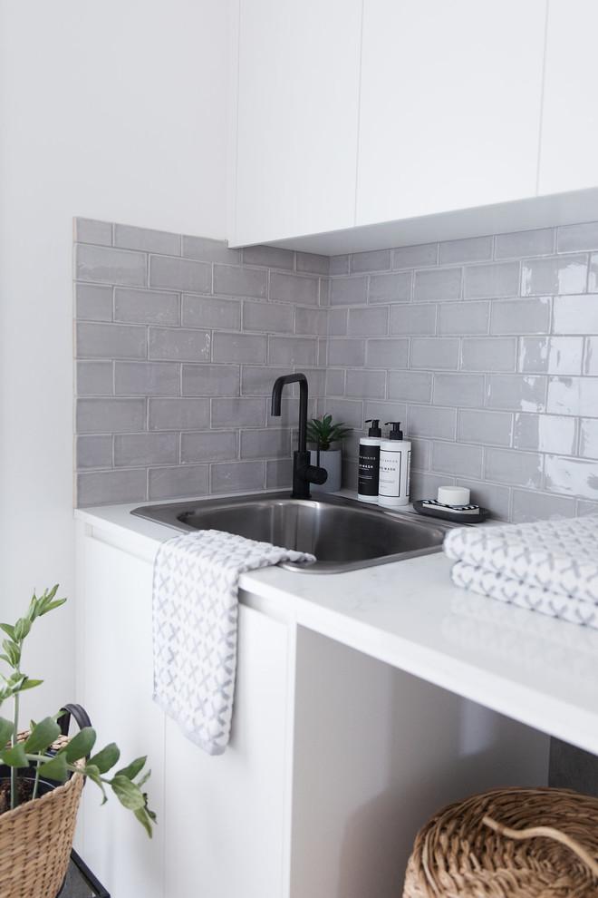 Ispirazione per una sala lavanderia minimalista di medie dimensioni con lavello da incasso, top in quarzo composito, pareti bianche, pavimento in gres porcellanato e pavimento grigio