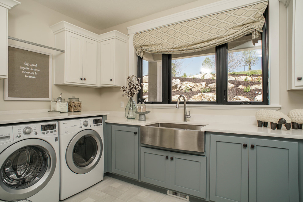 Laundry room - farmhouse gray floor laundry room idea in Salt Lake City with a farmhouse sink, shaker cabinets, blue cabinets, beige walls, a side-by-side washer/dryer and white countertops