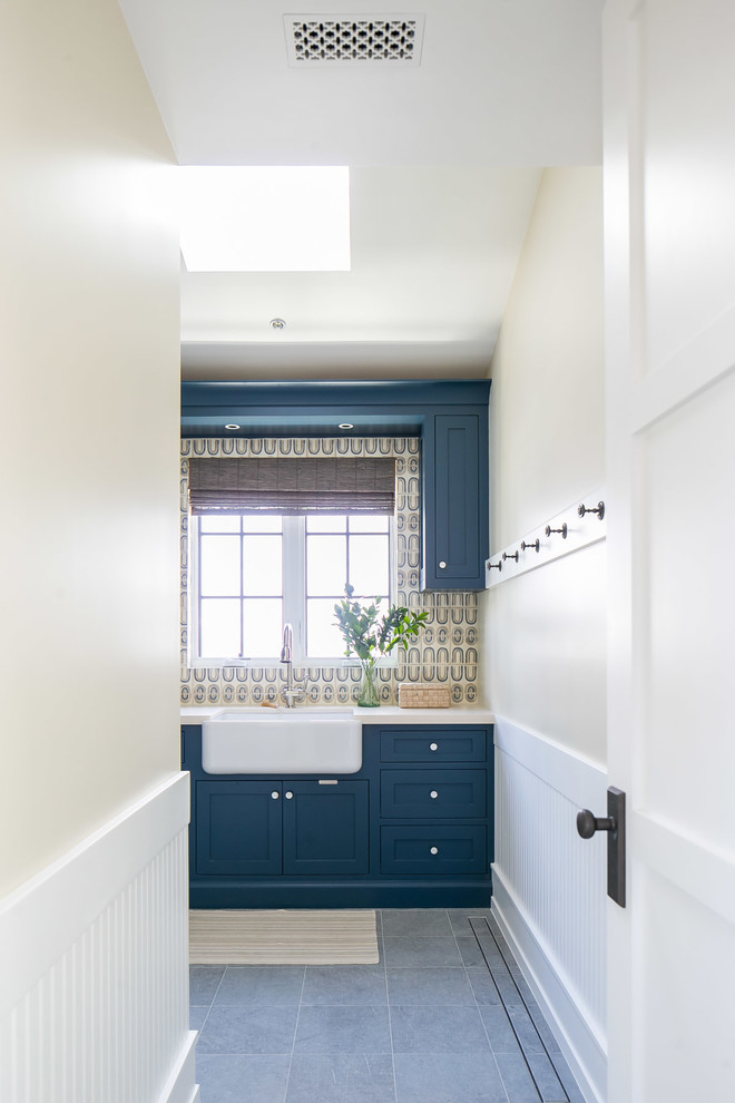 Example of a large island style l-shaped gray floor dedicated laundry room design in Orange County with a farmhouse sink, shaker cabinets, blue cabinets, a side-by-side washer/dryer, beige countertops and beige walls