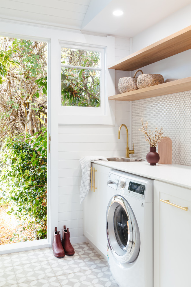 Photo of a country laundry room in Hobart with a drop-in sink, white walls, a side-by-side washer and dryer, grey floor and planked wall panelling.