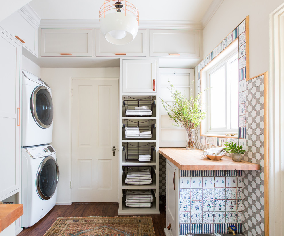 Inspiration for a mid-sized farmhouse dark wood floor laundry room remodel in Los Angeles with shaker cabinets, gray cabinets, wood countertops, white walls, a stacked washer/dryer and beige countertops