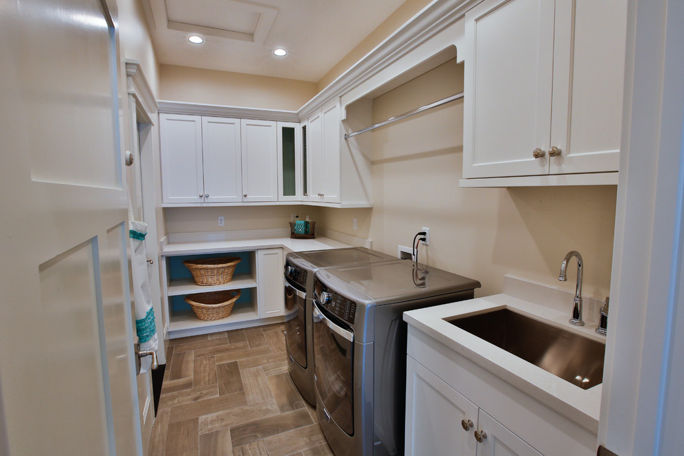 Dedicated laundry room - large transitional galley porcelain tile dedicated laundry room idea in Salt Lake City with an undermount sink, shaker cabinets, white cabinets, beige walls, a side-by-side washer/dryer and quartzite countertops