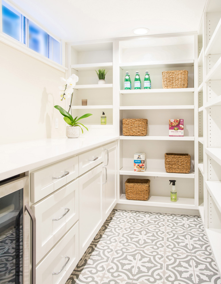 Dedicated laundry room - mid-sized farmhouse porcelain tile and gray floor dedicated laundry room idea in Seattle with a farmhouse sink, shaker cabinets, white cabinets, quartz countertops, white walls, a stacked washer/dryer and white countertops