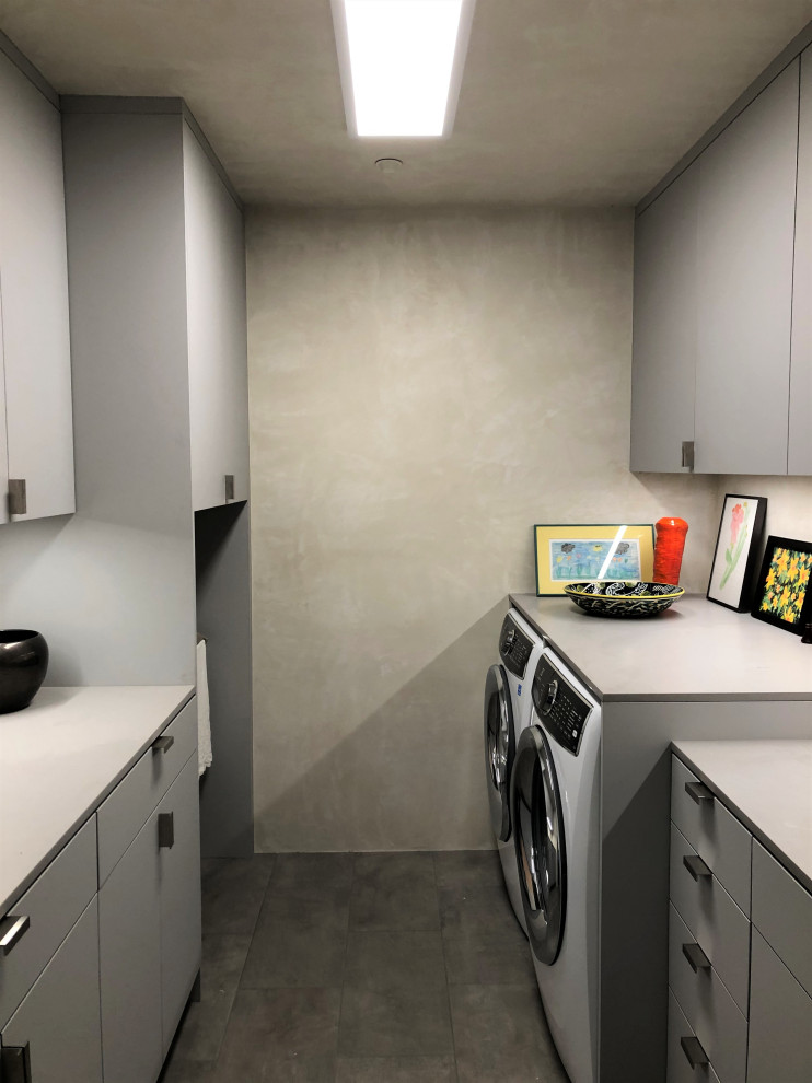 Mid-sized trendy galley gray floor dedicated laundry room photo in Other with an undermount sink, flat-panel cabinets, gray cabinets, beige walls, a side-by-side washer/dryer and gray countertops