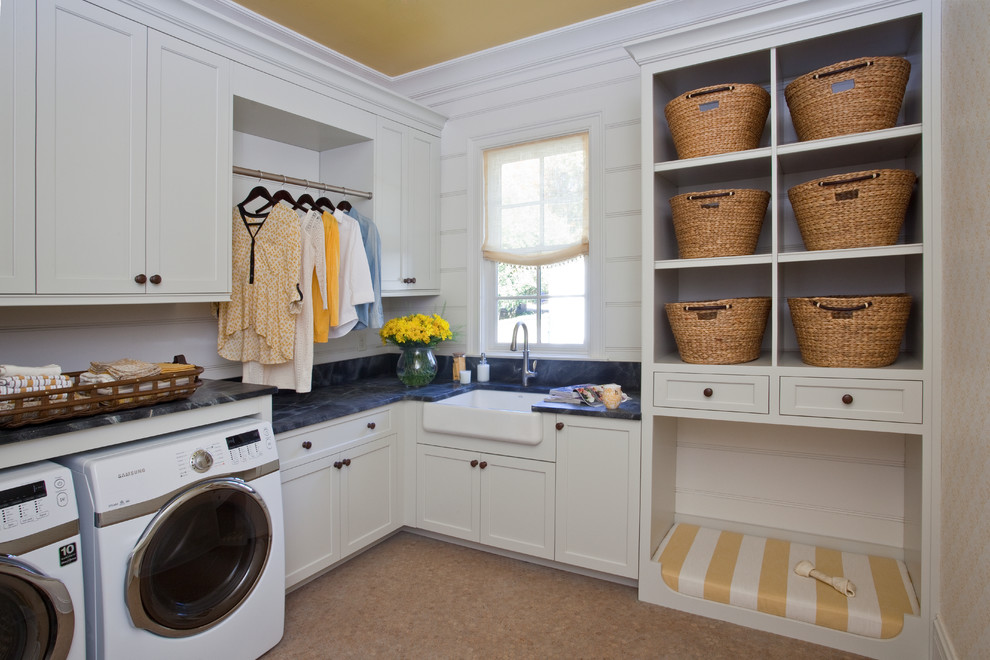 Transitional l-shaped cork floor dedicated laundry room photo in Other with a farmhouse sink, shaker cabinets, white cabinets, a side-by-side washer/dryer and black countertops