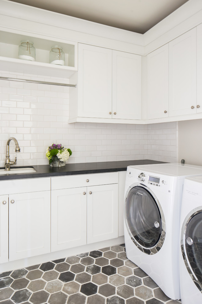 Elegant l-shaped multicolored floor dedicated laundry room photo in Orange County with an undermount sink, white cabinets, a side-by-side washer/dryer, black countertops, shaker cabinets and gray walls