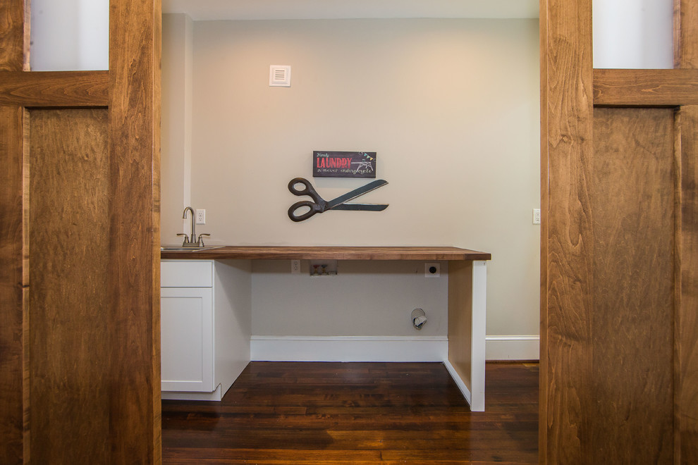 Inspiration for a mid-sized transitional dark wood floor and brown floor dedicated laundry room remodel in Richmond with a drop-in sink, shaker cabinets, white cabinets, wood countertops and gray walls