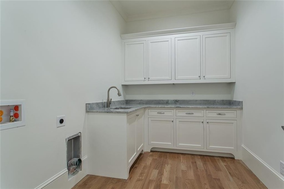 Large elegant u-shaped dedicated laundry room photo in Atlanta with recessed-panel cabinets, white cabinets, marble countertops, a side-by-side washer/dryer and gray countertops