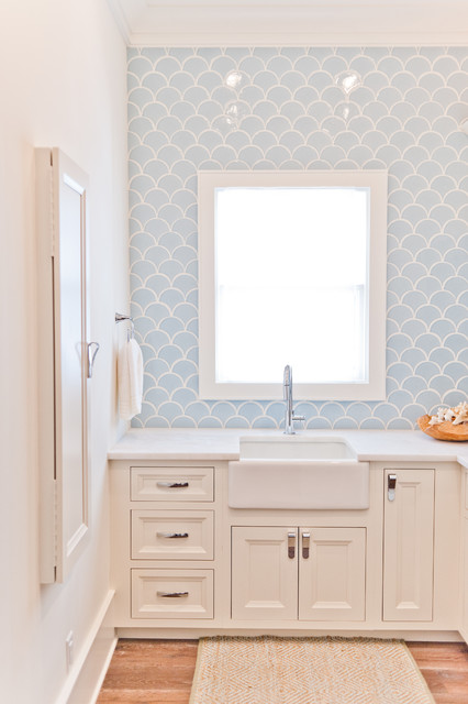 Example of a mid-sized coastal l-shaped light wood floor dedicated laundry room design in Jacksonville with a farmhouse sink, white cabinets, marble countertops, white walls, a stacked washer/dryer and recessed-panel cabinets