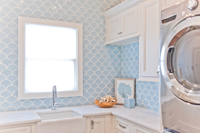 Inspiration for a mid-sized beach style l-shaped light wood floor dedicated laundry room remodel in Jacksonville with a farmhouse sink, white cabinets, marble countertops, white walls, a stacked washer/dryer and recessed-panel cabinets