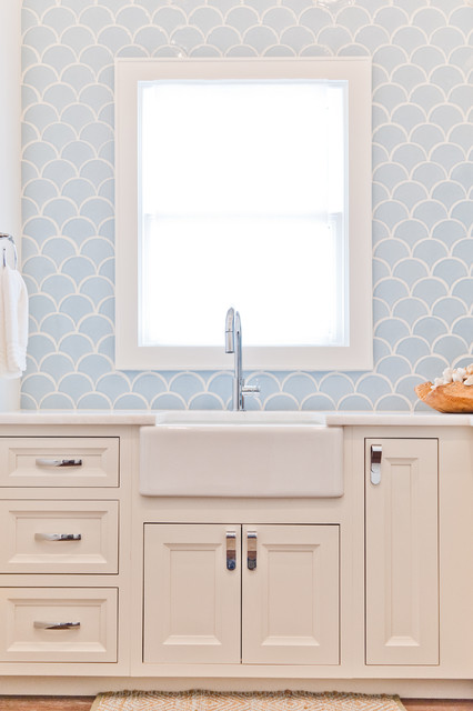 Example of a mid-sized coastal l-shaped light wood floor dedicated laundry room design in Jacksonville with a farmhouse sink, beaded inset cabinets, white cabinets, marble countertops, white walls and a stacked washer/dryer