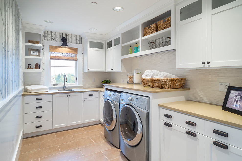 Example of a transitional l-shaped beige floor dedicated laundry room design in Portland with an undermount sink, white cabinets and a side-by-side washer/dryer
