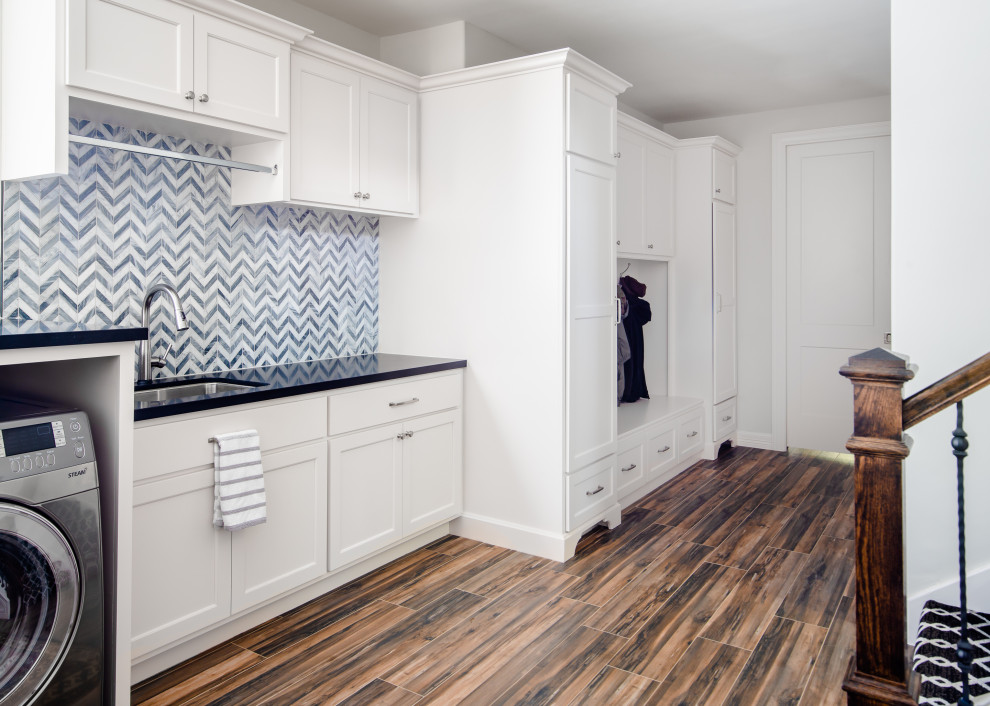 Laundry room - large transitional single-wall porcelain tile and brown floor laundry room idea in Houston with a single-bowl sink, shaker cabinets, white cabinets, granite countertops, gray backsplash, stone tile backsplash, white walls, a side-by-side washer/dryer and black countertops