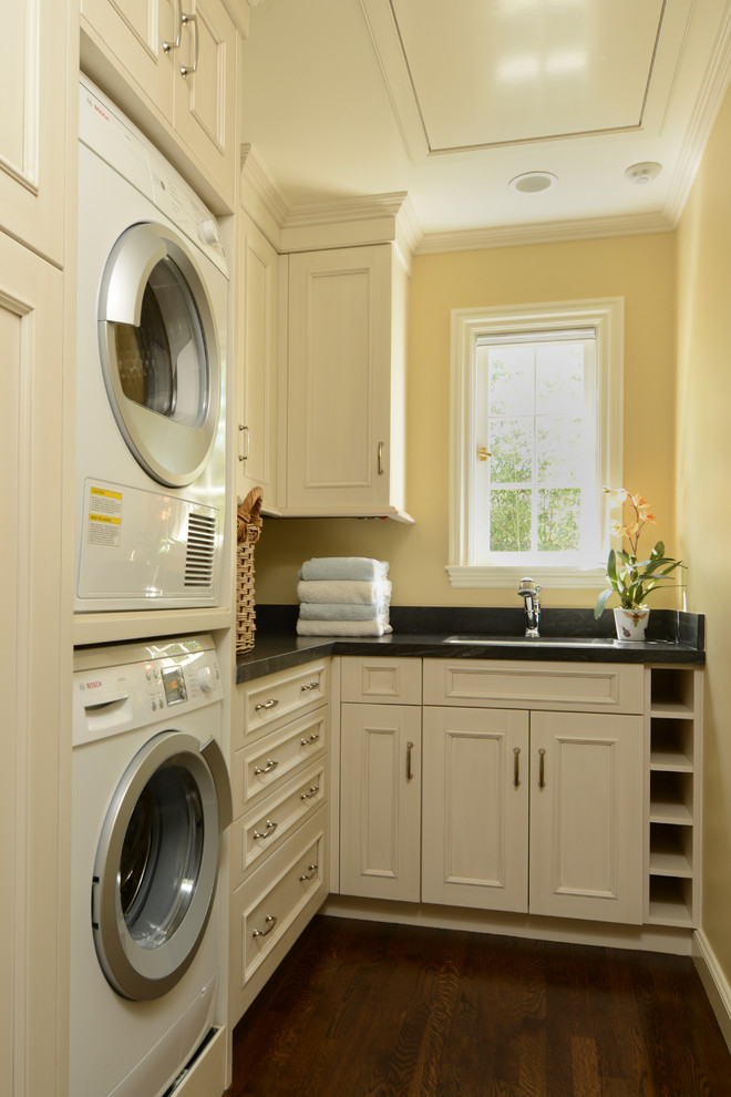 Elegant laundry room photo in San Francisco with a stacked washer/dryer, white cabinets, yellow walls and black countertops