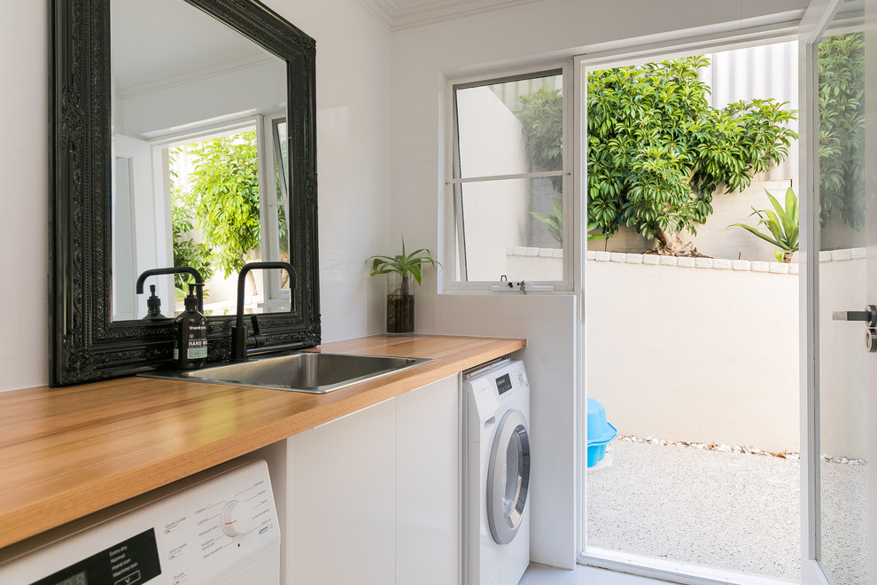 Inspiration for a contemporary single-wall dedicated laundry room in Perth with a drop-in sink, flat-panel cabinets, white cabinets, wood benchtops, white walls and brown benchtop.