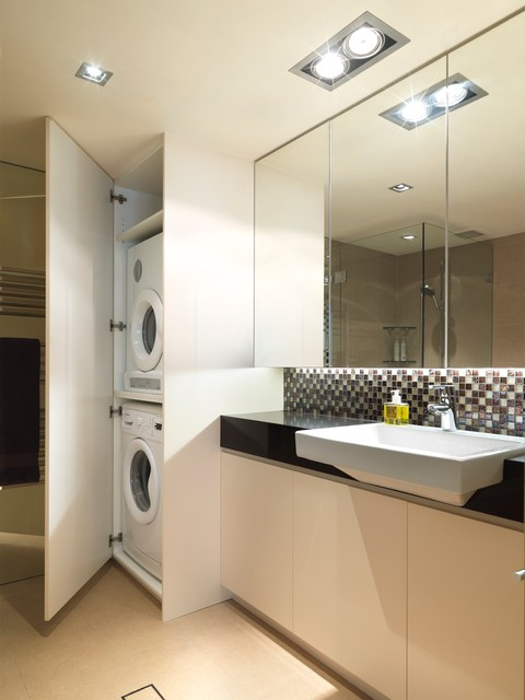 Inspiration for a medium sized contemporary utility room in Sydney with flat-panel cabinets, white cabinets and a stacked washer and dryer.
