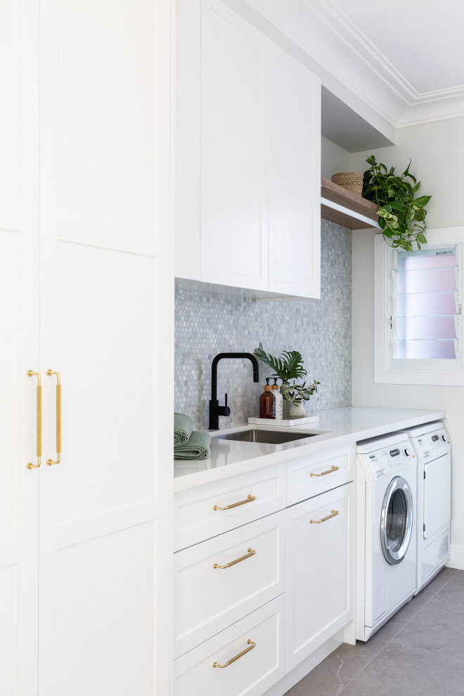 Design ideas for a mid-sized beach style dedicated laundry room in Sydney with a single-bowl sink, shaker cabinets, white cabinets, quartzite benchtops, marble splashback, white walls, porcelain floors, a side-by-side washer and dryer, white benchtop, grey splashback and grey floor.