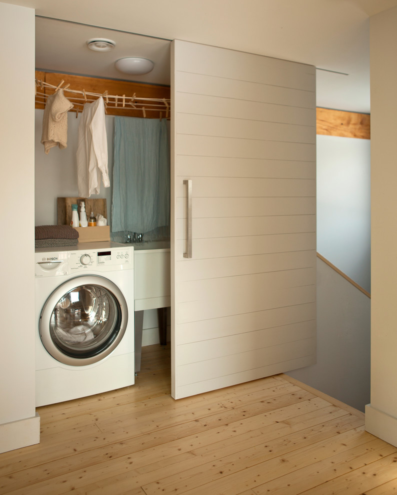 Inspiration for a contemporary laundry room remodel in Portland Maine with white walls
