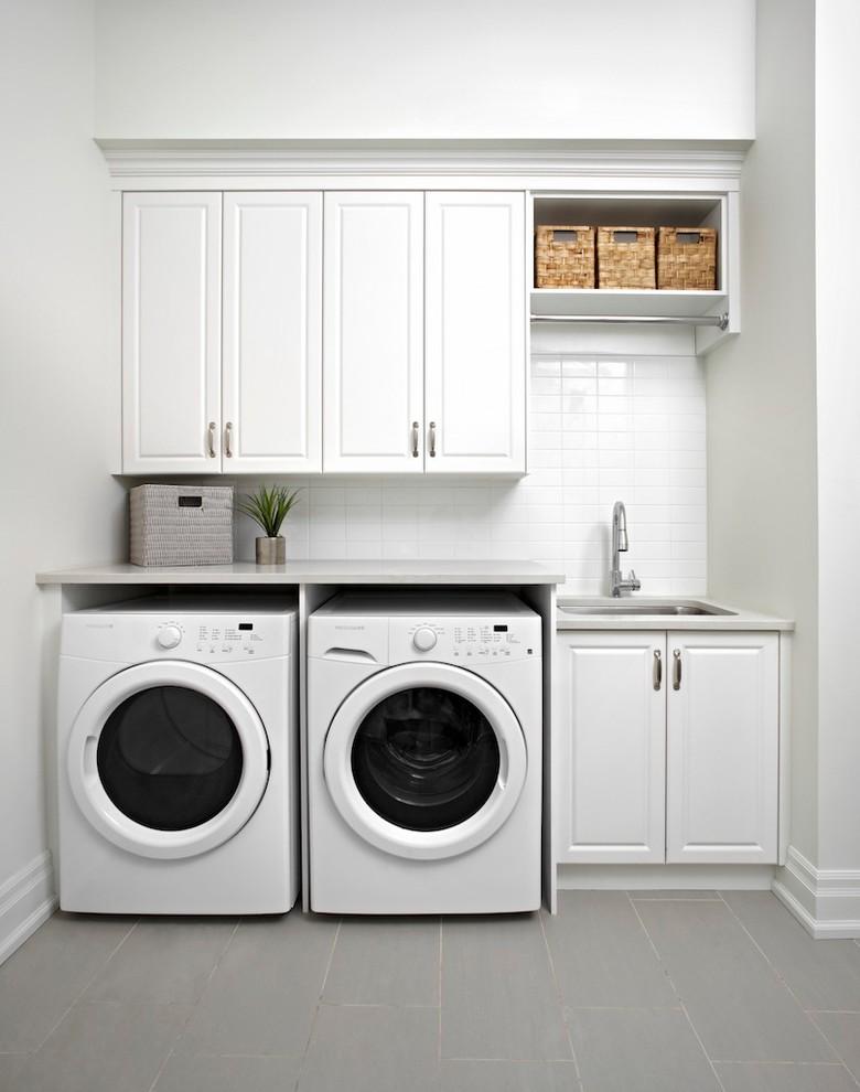 Klassisk inredning av en grå linjär grått tvättstuga, med en undermonterad diskho, luckor med upphöjd panel, vita skåp, vita väggar och en tvättmaskin och torktumlare bredvid varandra