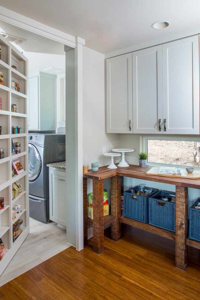 Utility room - mid-sized transitional single-wall medium tone wood floor and brown floor utility room idea in Austin with shaker cabinets, white cabinets, wood countertops, white walls and a side-by-side washer/dryer