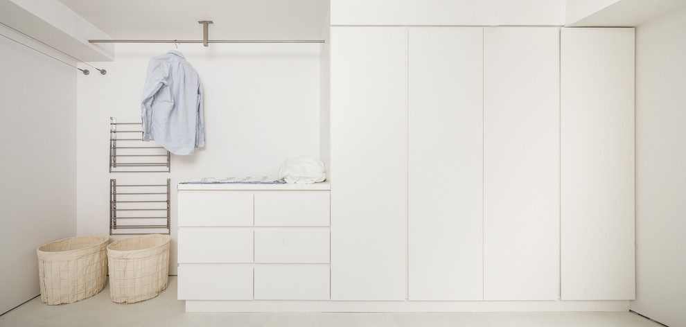 Example of a minimalist laundry room design in Philadelphia with flat-panel cabinets, white cabinets, white walls and a side-by-side washer/dryer