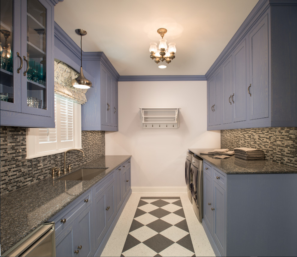 Utility room - small traditional galley porcelain floor utility room idea in Houston with a drop-in sink, recessed-panel cabinets, blue cabinets, granite countertops and white walls