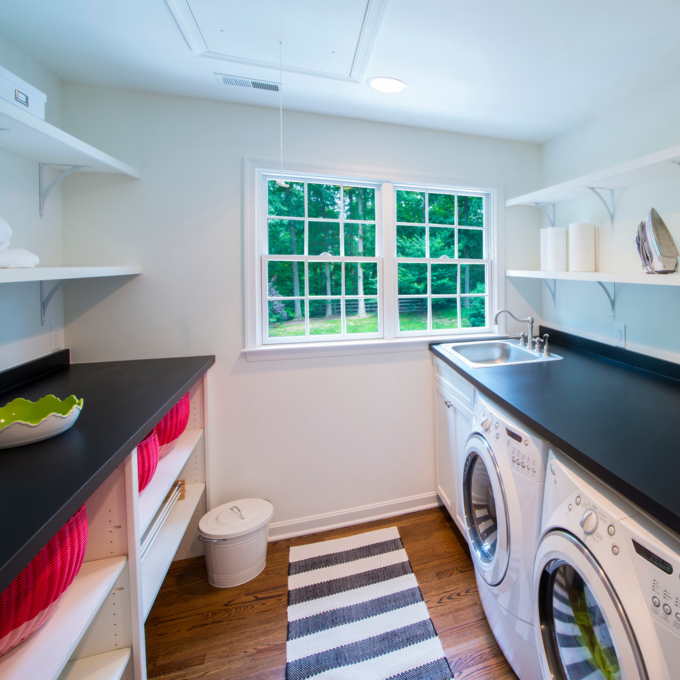 Example of a classic laundry room design in Baltimore with a drop-in sink, white cabinets and black countertops