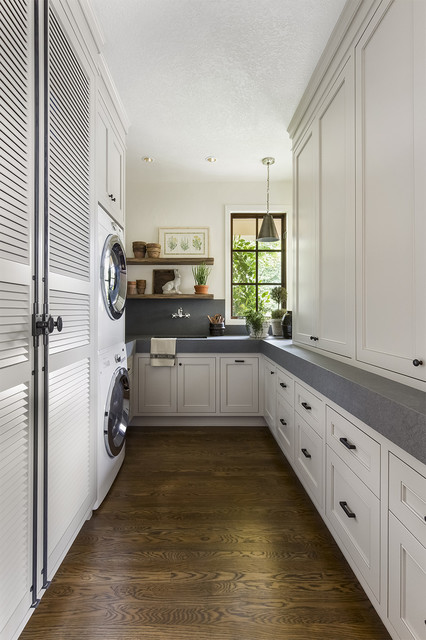 Photo of a traditional u-shaped laundry room in Portland with an undermount sink, recessed-panel cabinets, white cabinets, white walls, dark hardwood floors, a stacked washer and dryer and grey benchtop.