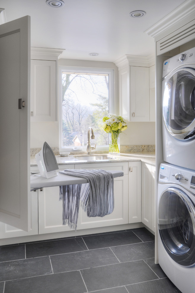 Mid-sized transitional u-shaped slate floor dedicated laundry room photo in Toronto with a stacked washer/dryer, white cabinets, an undermount sink, recessed-panel cabinets, granite countertops and beige countertops