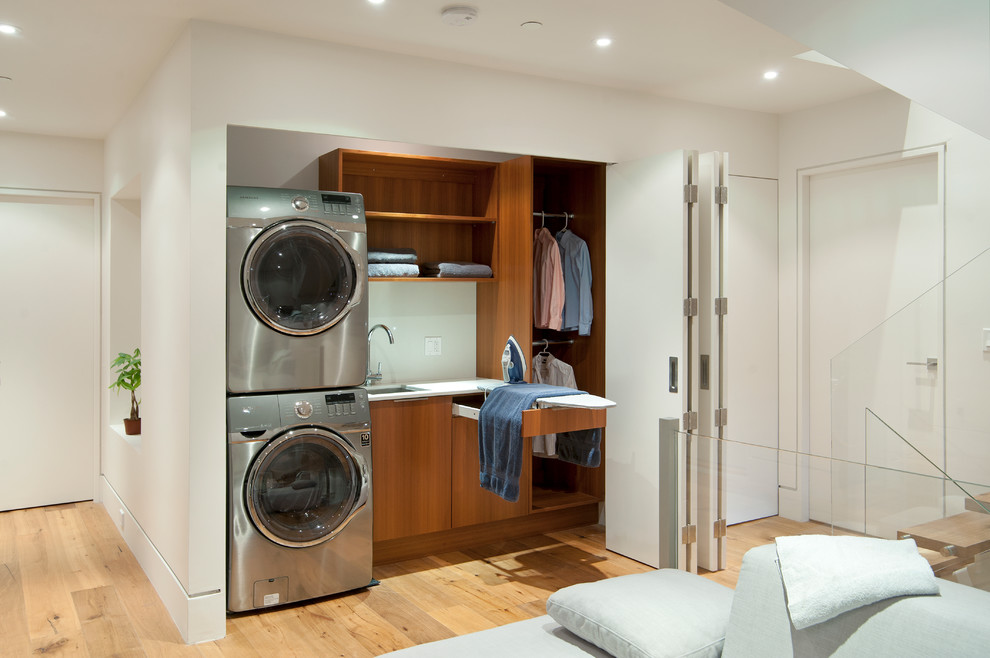 Laundry closet - contemporary single-wall medium tone wood floor laundry closet idea in Vancouver with an undermount sink, flat-panel cabinets, medium tone wood cabinets, white walls, a stacked washer/dryer and white countertops