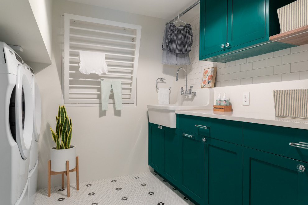 Mid-sized transitional galley ceramic tile and white floor dedicated laundry room photo in New York with a farmhouse sink, shaker cabinets, green cabinets, quartz countertops, white backsplash, quartz backsplash, white walls, a side-by-side washer/dryer and white countertops