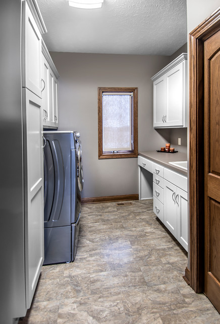 Dedicated laundry room - mid-sized linoleum floor dedicated laundry room idea in Other with recessed-panel cabinets, white cabinets, laminate countertops, gray walls and a side-by-side washer/dryer