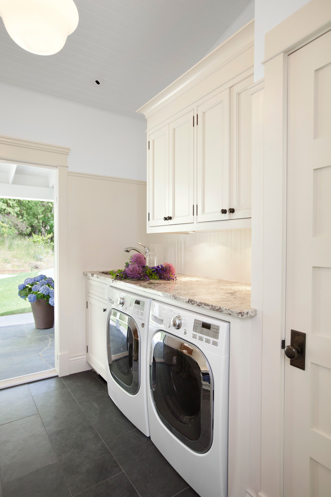 Inspiration for a timeless black floor laundry room remodel in Vancouver with recessed-panel cabinets, beige cabinets and beige countertops