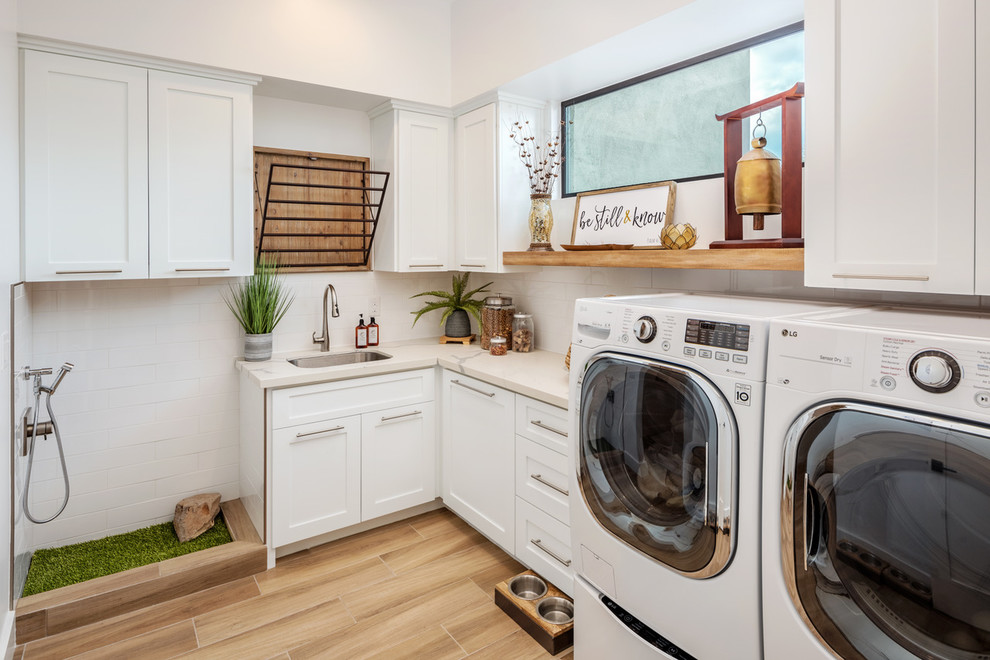 Example of a transitional l-shaped beige floor utility room design in Phoenix with an undermount sink, shaker cabinets, white cabinets, white walls, a side-by-side washer/dryer and white countertops