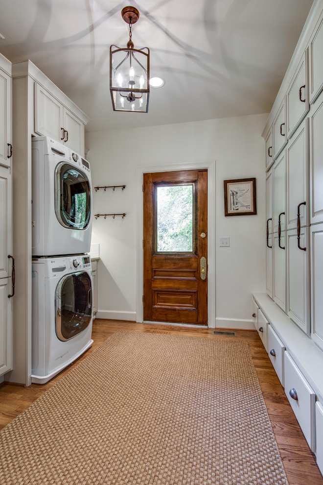 Utility room - large cottage galley medium tone wood floor and brown floor utility room idea in Nashville with recessed-panel cabinets, white cabinets, granite countertops, white walls, a stacked washer/dryer and beige countertops